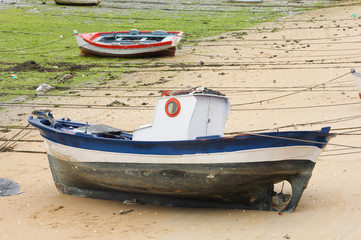 Boat and little fishing ship on the sand with low tide