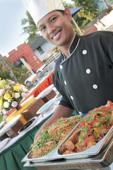 chef carrying food at buffet
