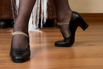Feet and shoes of a spanish dancer on a wooden floor