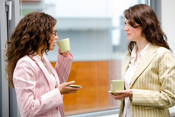 Young businesswomen having break at office drinking coffee