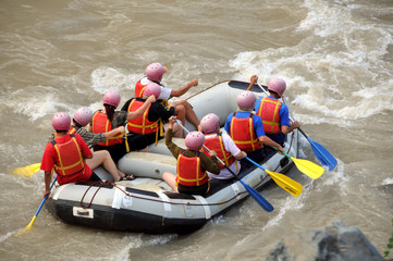 Group of tourists rafting down a  mountain river in a boat.