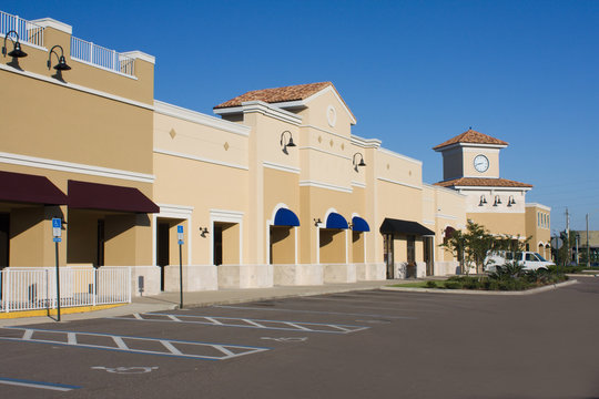 upscale pastel strip mall with awnings and corner clock tower