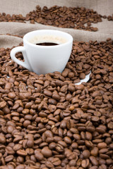 cup of coffee over coffee beans