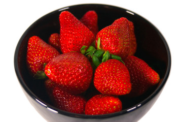 A bowl of bright red strawberries in a black bowl