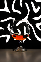 glass of brandy against black-and-white background