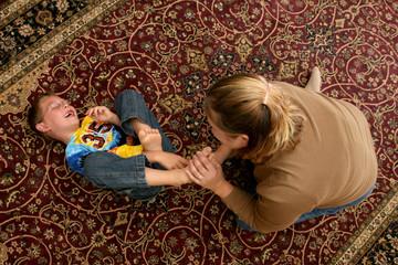 mother tickling her son's bare feet on the floor