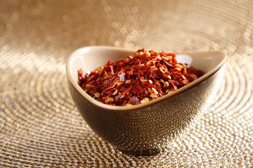 crushed red hot chilli pepper in bowl on golden background