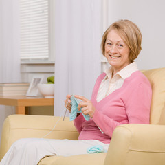 Relaxed senior woman knitting on sofa at home