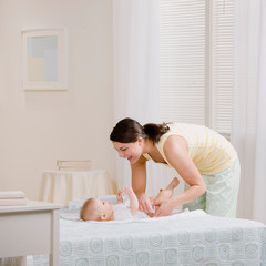 Loving mother changing babyÕs diaper on bed