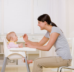 Mother feeding hungry baby in highchair in kitchen