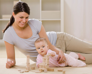 mother and baby playing with blocks on livingroom floor