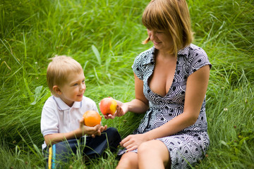 Mother and the son hold an apple and an orange in hands.