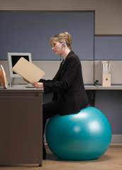 Businesswoman looking at file folder sitting on exercise ball
