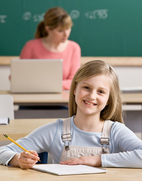 Student in classroom with teacher in the back