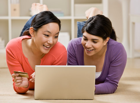 Friends using credit card to purchase goods on the internet