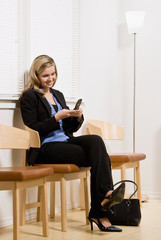 Businesswoman waiting for appointment text messaging on phone
