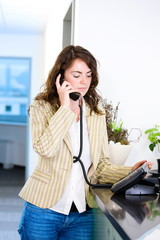 female receptionist receiving phone calls at office reception.