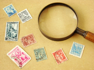 World postage stamps and magnifying glass on aged background