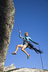 Female rock climber rappelling.