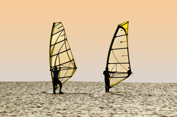 Silhouettes of two windsurfers on waves of a gulf