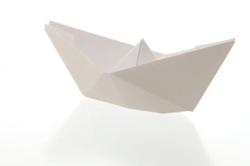 Paper boat on reflecting white background