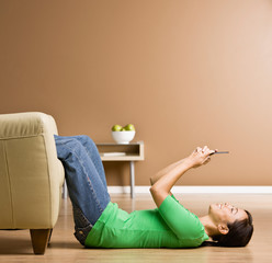Woman laying on floor in livingroom text messaging on cell phone