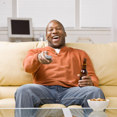 Man holding remote control and beer watching television