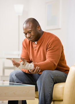 Frustrated man with splint in pain from injury to his wrist