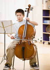 Musician practices performing on cello with sheet music