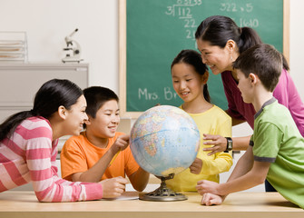 Teacher and students viewing globe in geography classroom