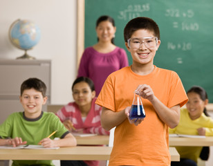 Student wearing goggles holds beaker of liquid in classroom