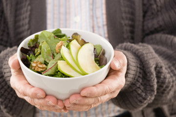 Man holding fresh, wholesome fruit salad