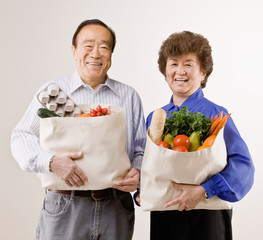 Couple holding grocery bag full of fresh fruits and vegetables