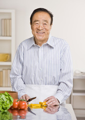 Man preparing wholesome salad in kitchen for dinner