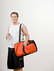 Confident athlete holding gym bag and water bottle