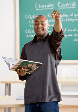 Teacher holding text book pointing to student in classroom