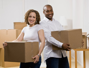 Couple moving into new home carrying cardboard boxes