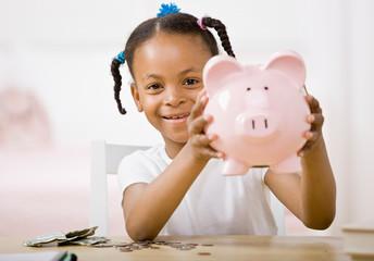 Girl putting money into piggy bank for future savings