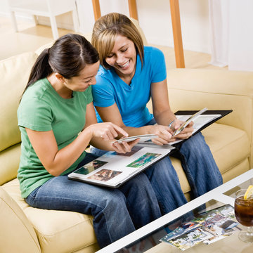 Friends sitting in livingroom looking at photograph album