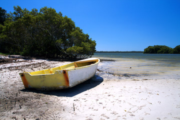 A lonely yellow boat on the beach