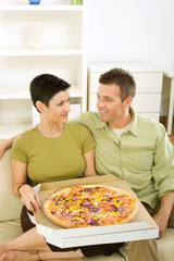 Couple sitting on sofa and eating pizza at home.