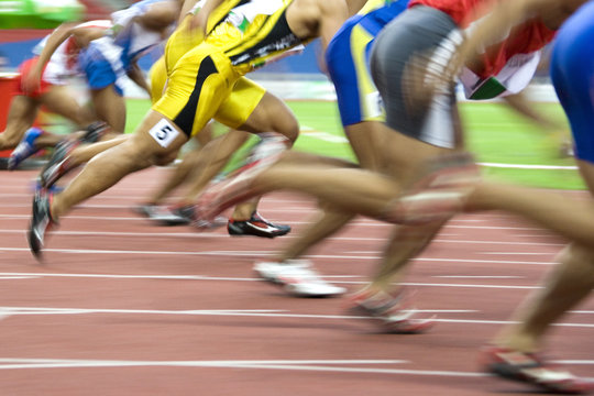 100 meters athletes in action with intentional blurring.