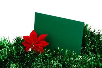 Green garland with red poinsettia and blank card on white