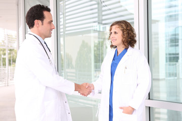 A man and woman medical team at hospital shaking hands