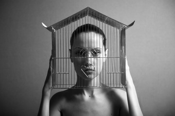 Surrealistic portrait of young woman with cage.