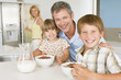 Father With Children As They Eat Breakfast And Mother In The Bac