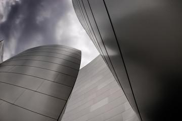 nowoczesny budynek z krzywego metalu na ciemnym pochmurnym niebie - 9802717