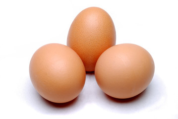 Three free range eggs on a white linen background