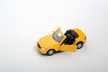 A simple yellow toy car on white background