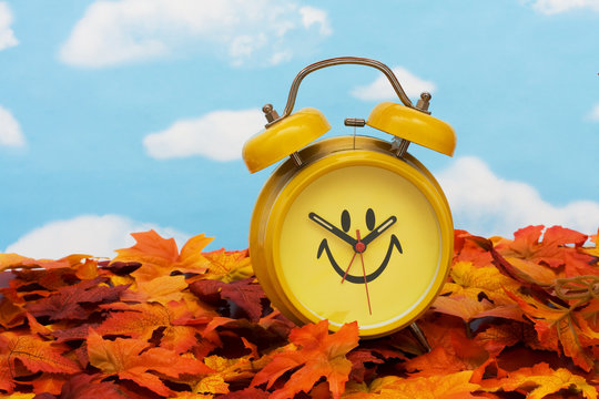 Fall leaves with yellow clock , fall back time change